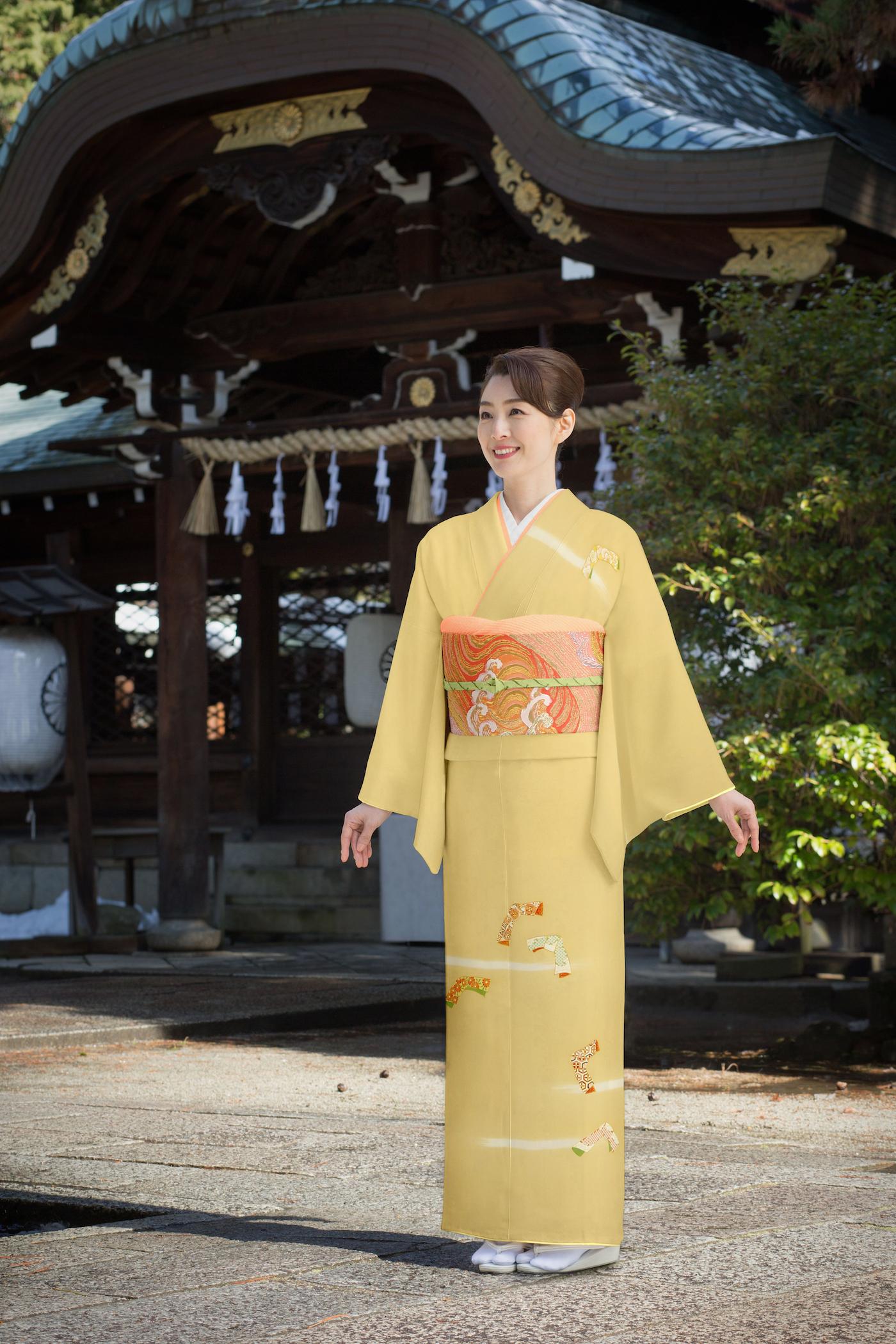 付け下げで神社の前にたたずむ女性
