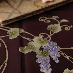 訪問着「葡萄唐草」栗皮茶色。盡政金唐錦袋帯「北欧瑞華紋」紫鳶色、白と朱の帯締めをコーディネートして。上前を下から1。