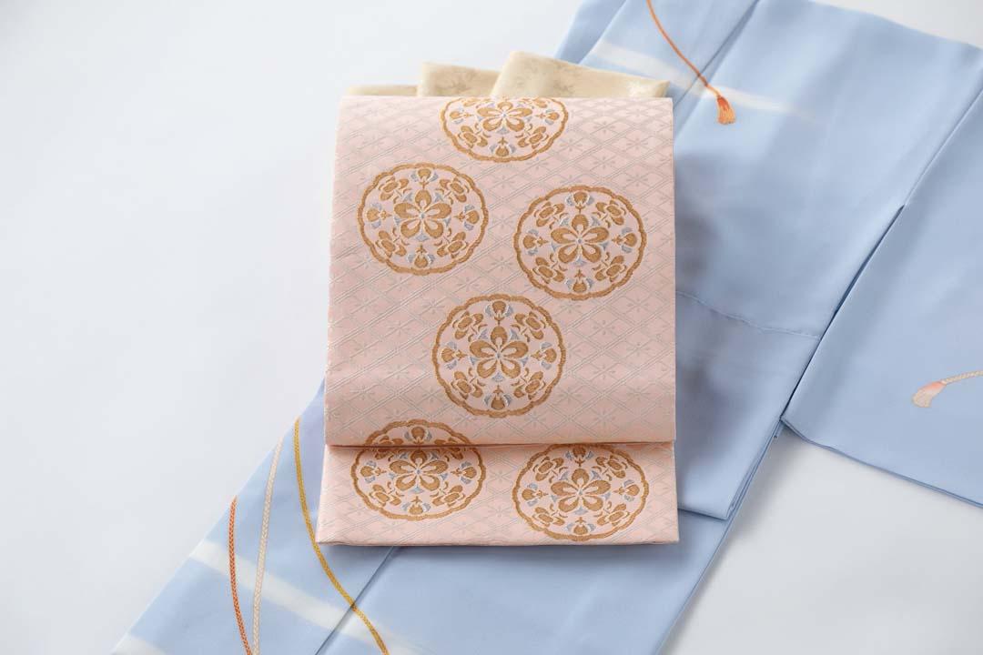 セミオーダー訪問着「紐に霞」うす花色。有職織物「梅華文」珊瑚色、金茶色の帯揚げを合わせて。お太鼓中心。