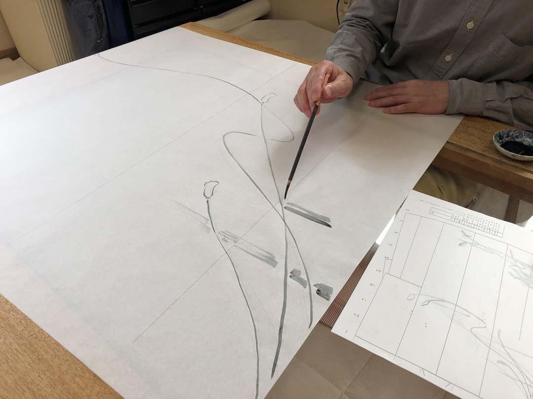 セミオーダー訪問着「紐に霞」下絵のあたりを描いている下絵職人。