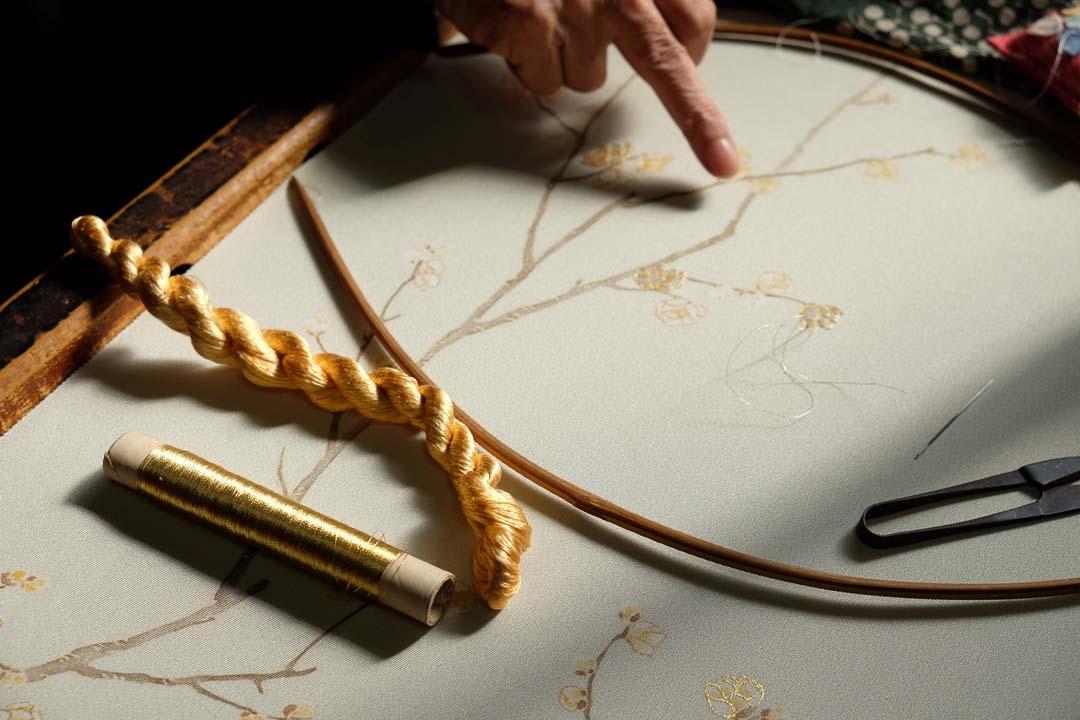 訪問着「蝋梅」の刺繍をする職人。