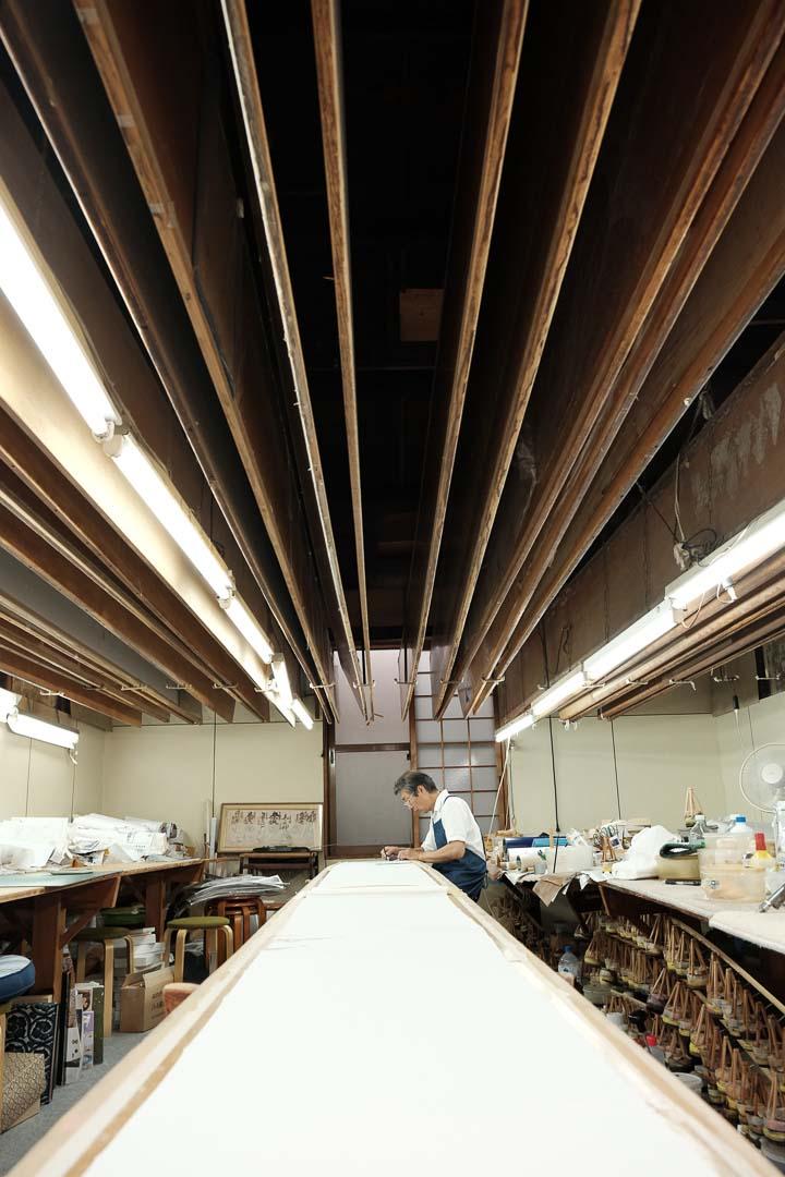摺り疋田職人の仕事場。長いもみの木を使った板の上に白生地を貼って作業する。
