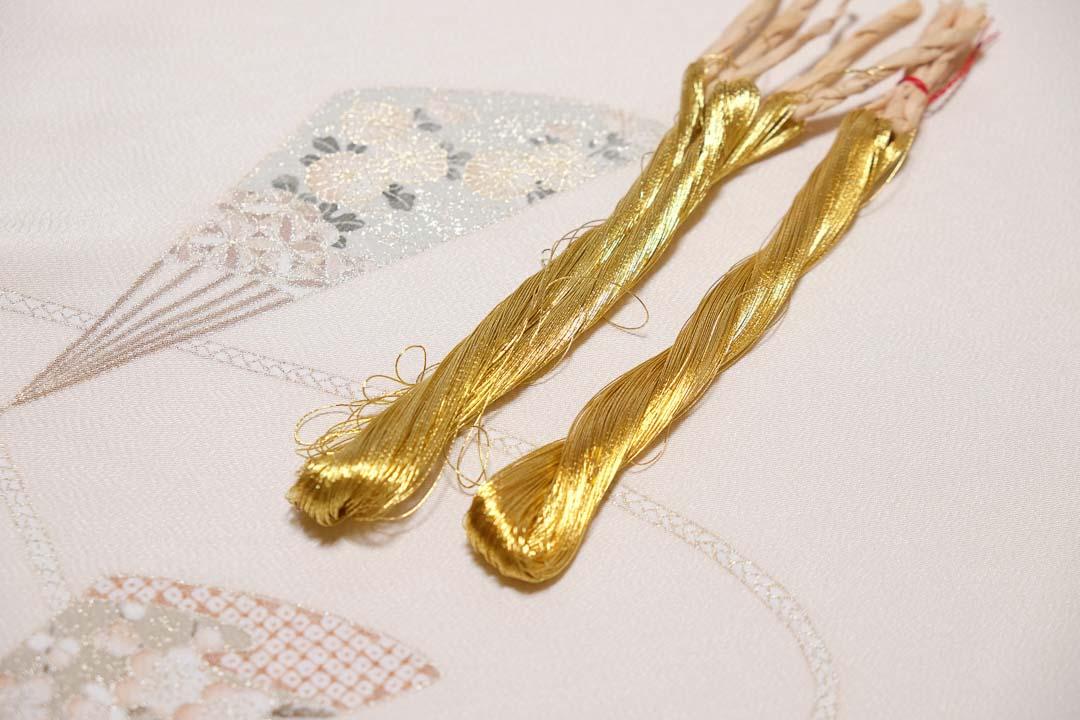 訪問着「扇子に紐」白茶色の刺繍をしている様子。金糸の色味を比べて。