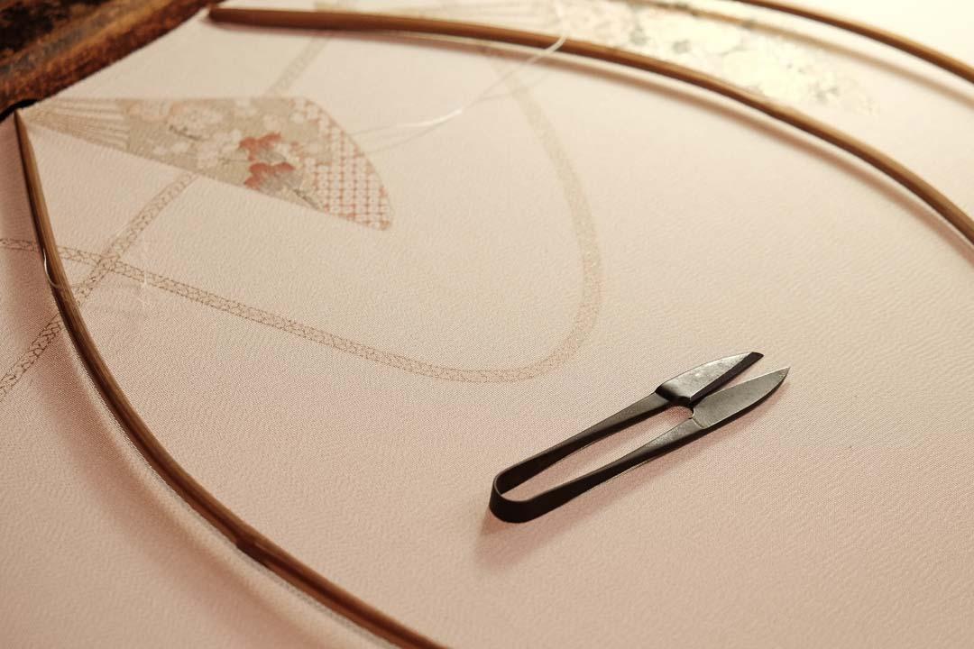 訪問着「扇子に紐」白茶色の刺繍をしている様子。糸切り鋏。