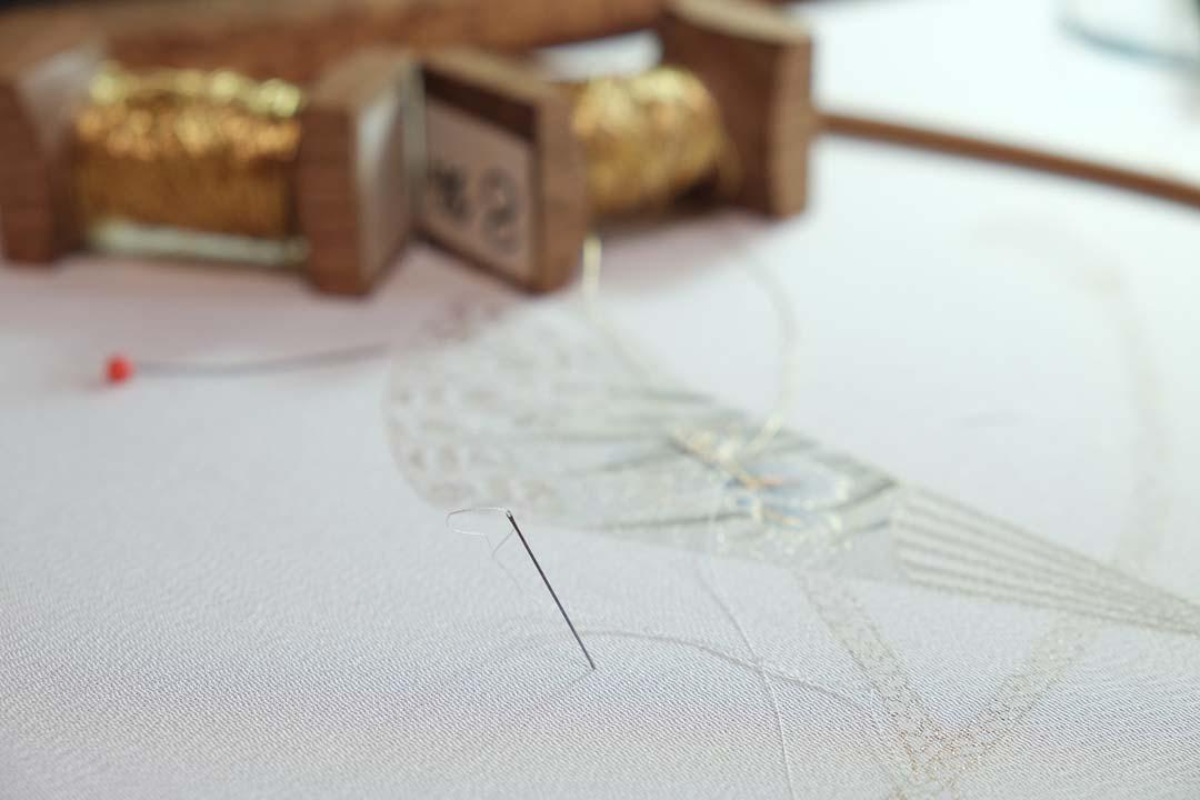 訪問着「扇子に紐」白茶色。あやめの金駒刺繍をしている様子。針。