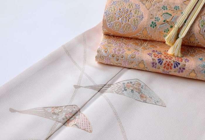 訪問着「扇子に紐」白茶色に、盡政金唐錦袋帯「正倉院撥鏤文」、承和色の帯締めをコーディネート。上前斜め下のアングルから。