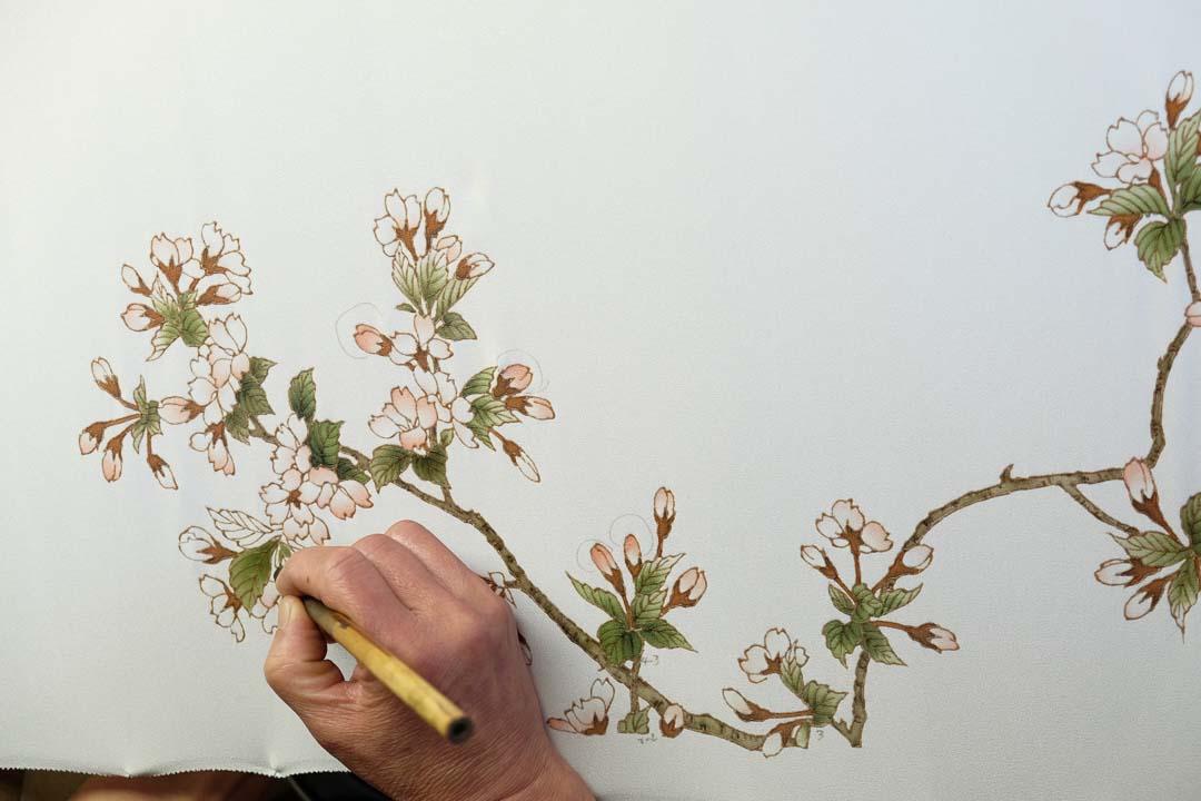 訪問着「山桜」の友禅染めをやる職人の手。真俯瞰。
