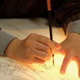 下絵職人が桜の柄の下絵を筆で描いているところ。八掛を描いているので下から光をあてて。
