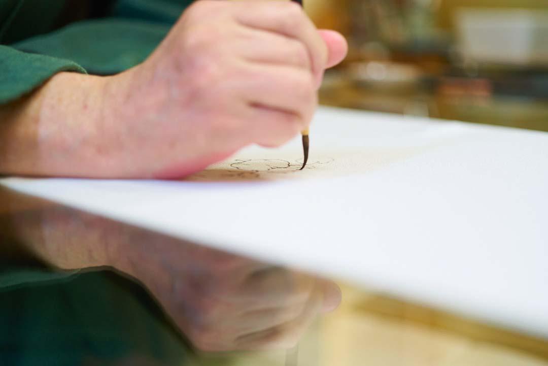 下絵職人が描くあやめ。筆がしなっている。