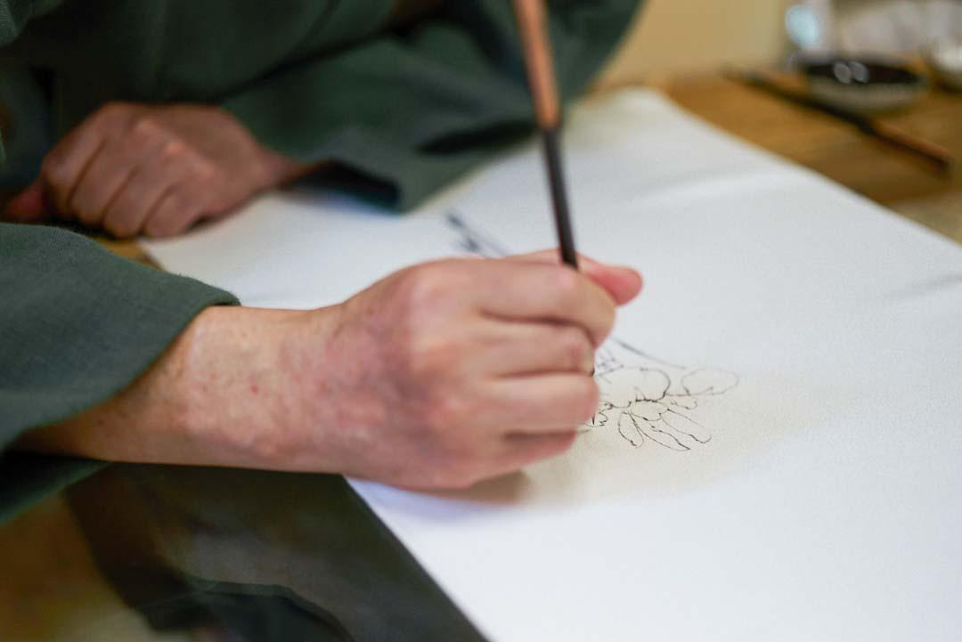 下絵職人が白生地に代用青花であやめを描く様子。