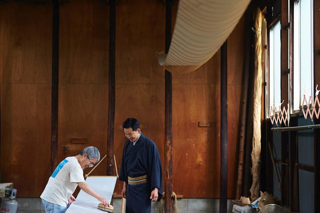 地入れ職人の仕事場で、京ごふく二十八代表の原巨樹が職人さんと談笑する様子。