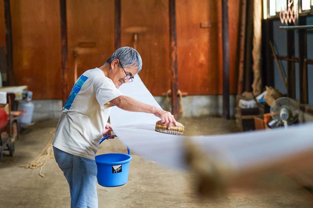 夏場に地入れ職人が平刷毛とバケツを持って土間で作業をしている様子。