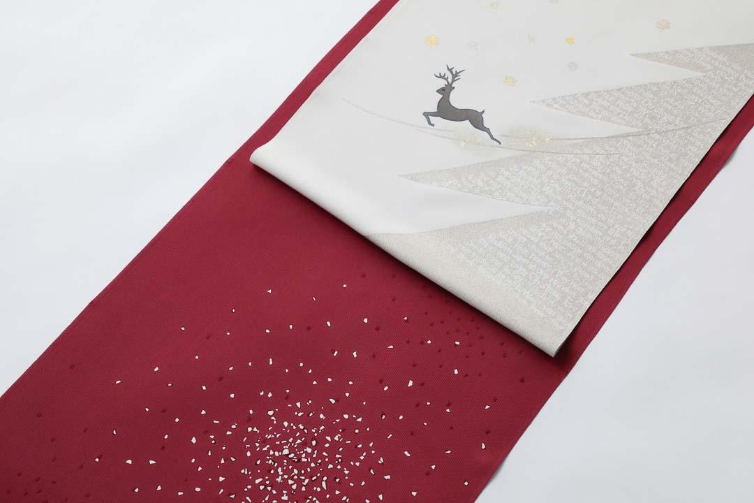 染め名古屋帯「クリスマス」のお太鼓。トナカイとクリスマスツリーに、ワイン色に染めた蒔き糊の着物を合わせて。