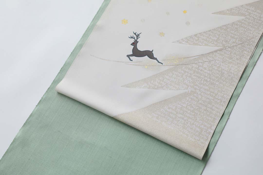 染め名古屋帯「クリスマス」のお太鼓。トナカイとクリスマスツリーに、浅緑色に染めた紬の着物を合わせて。