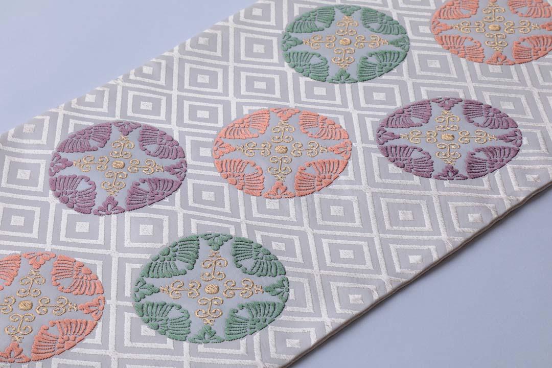 有職織物。二陪織物の臥せ蝶の丸文、白茶地、帯のみ全景。