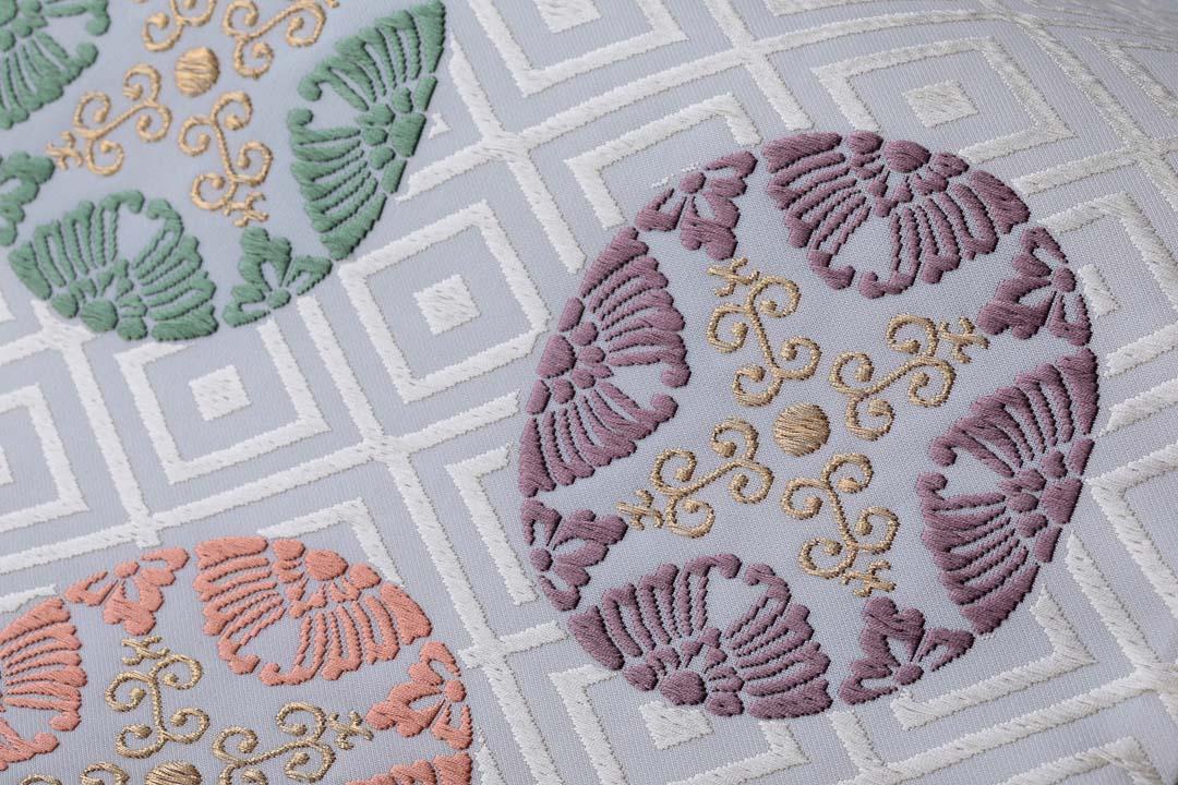 有職織物。二陪織物の臥せ蝶の丸文、白茶地、紫のアップ。