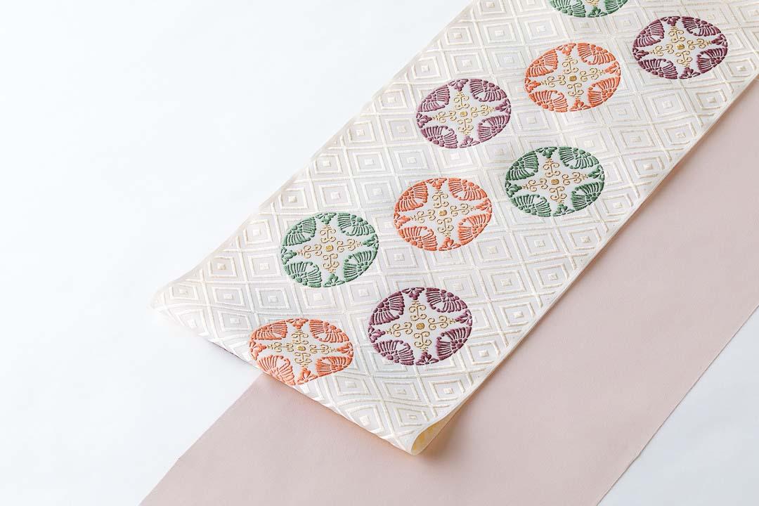 有職織物。二陪織物の臥せ蝶の丸文、白茶地。ピンクの色無地に合わせて。